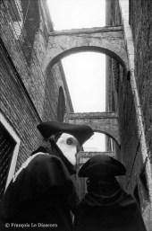Ref VENISE 12 – Deux personnages de carnaval passant sous des arches